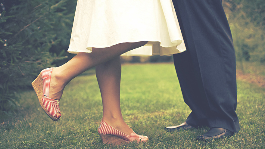 Shot of a couple's feet on grass - woman has one foot raised