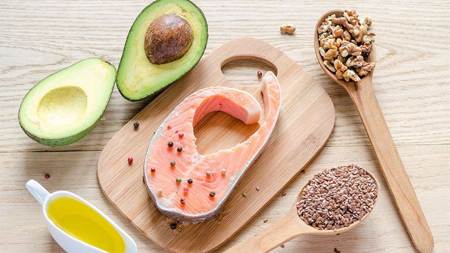 Chopping board with a salmon fillet, avocado, olive oil and wooden spoons containing seeds and nuts