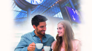 Smiling couple having coffee at train station