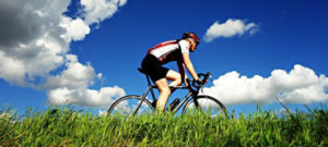 Person riding bike against very blue sky