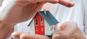 A little wooden house - red, white and blue - being cradled between a pair of hands
