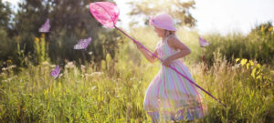 Small girl running in field with butterfly net