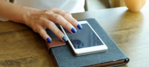 Woman with blue nail polish on iPhone