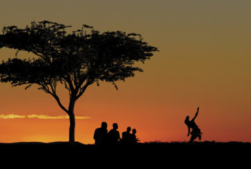 Cover of Listen To The Drums - a tree and a group of people silhouetted against a sunset in a cleat sky