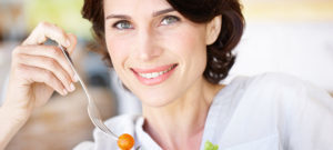 A beautiful woman eating a bowl of salad