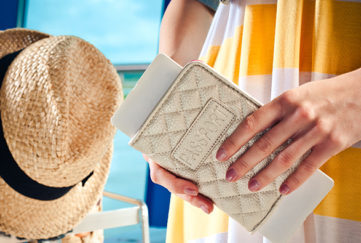 Close up of female hands holding passport and boarding pass with luggage trolley in the background.