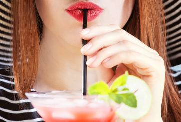 young woman in sunhat drinks cocktail