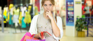 Portrait of thoughtful beautiful person holding open wallet with pensive expression in shopping center with shops on background. Young woman with paper bags deciding on expenses during shopping time