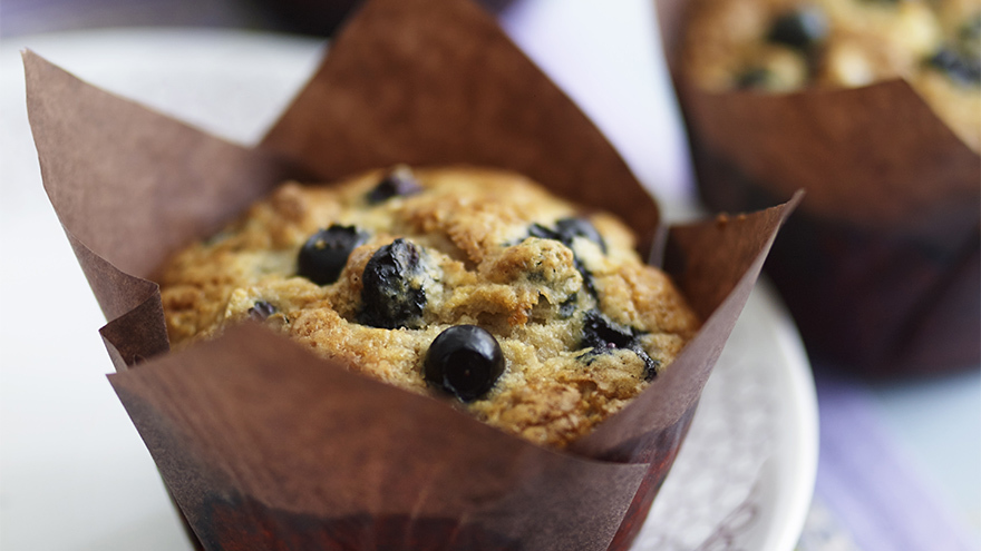 Freshly baked blueberry muffins in brown tulip shaped paper cases