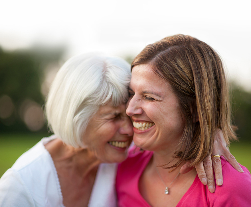 senior mother and mature daughter laughing and hugging