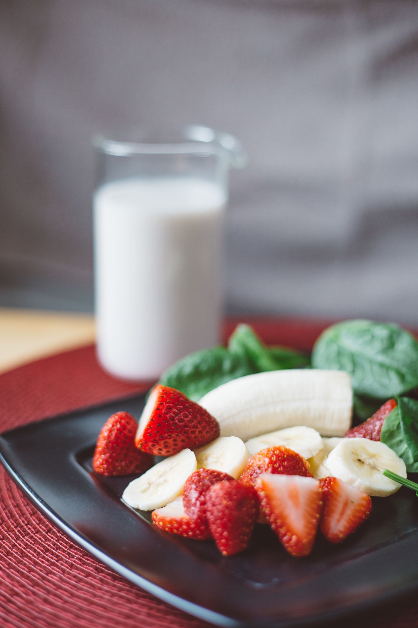 Glass of milk with banana and strawberries