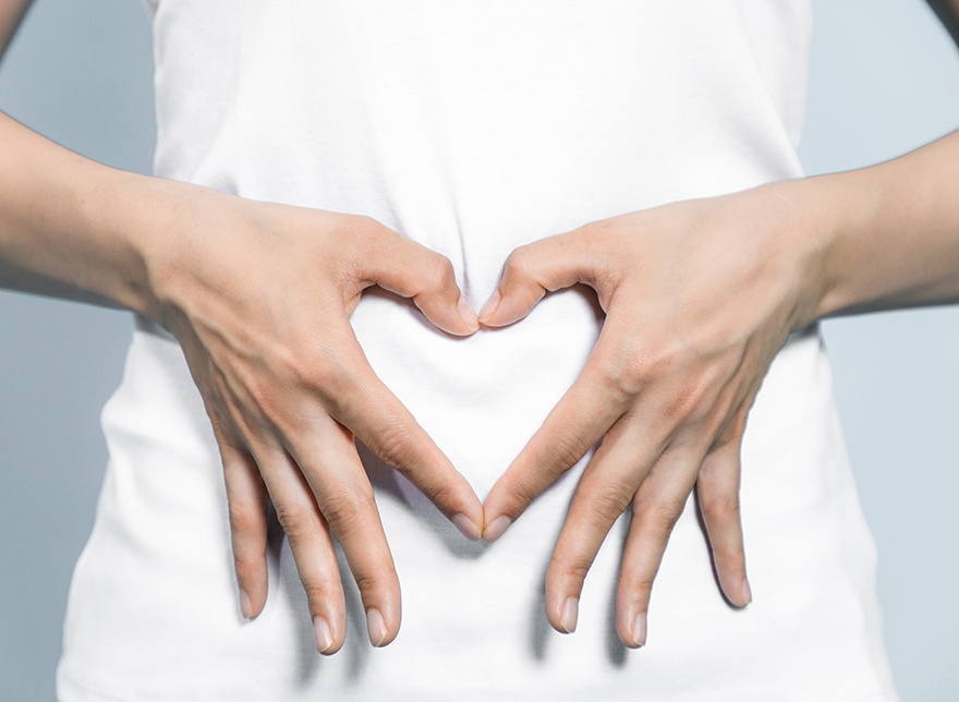 woman making heart shape with hands over her tummy