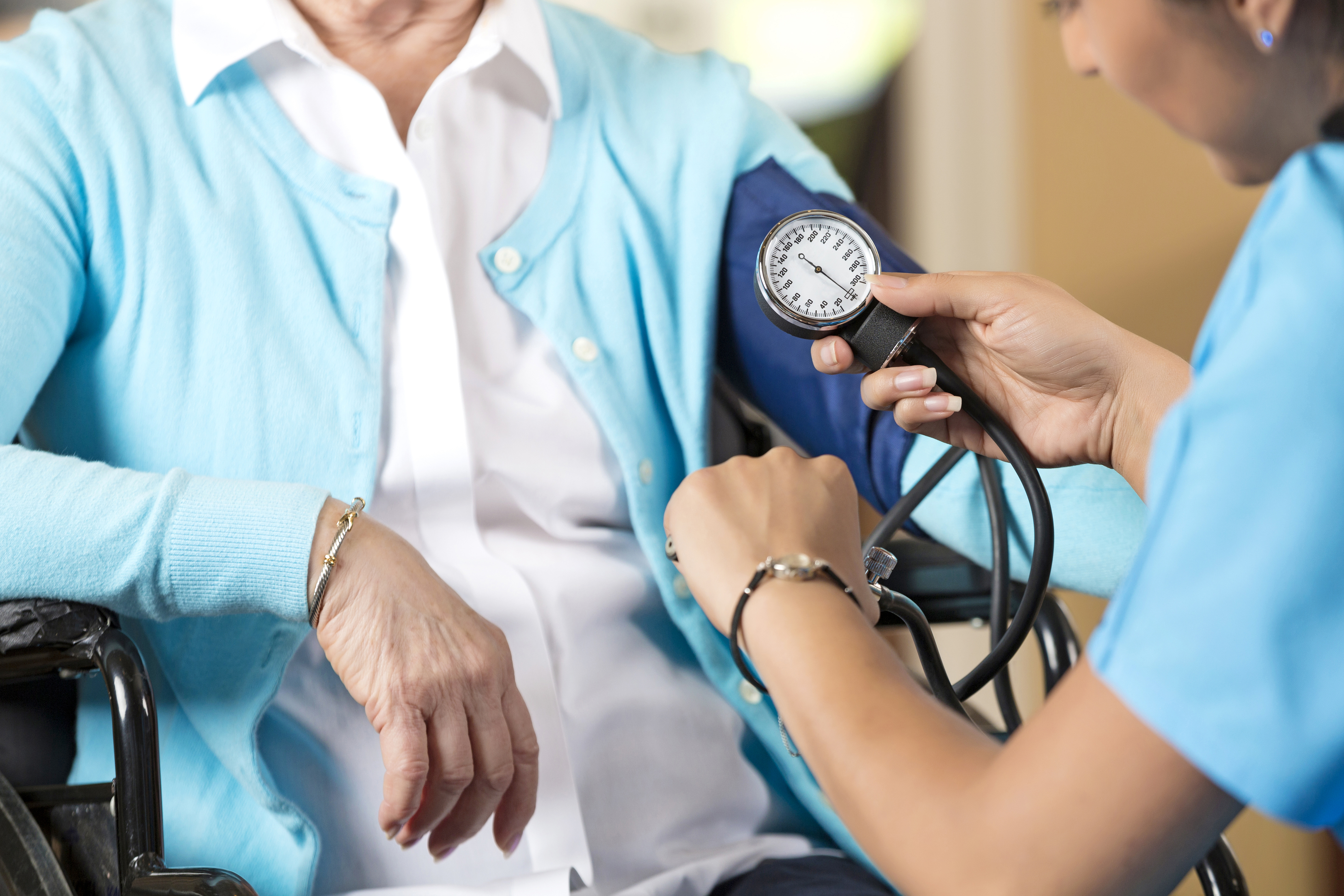 Close up of hands while nurse takes blood pressure of the woman sitting in the wheelchair in front of hair. Senior caucasian woman and a young hispanic woman. They are indoors, sitting down. The nurse is looking at her watch as she is working. The senior woman is wearing a white shirt with a light blue cardigan on top of it, the nurses scrubs are nearly the same color as the womans cardigan.