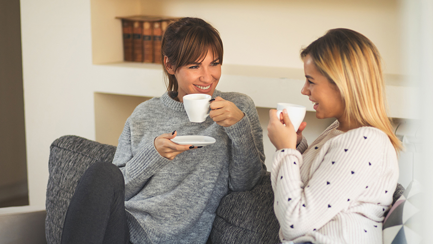 Two female friends enjoying coffee and small talk