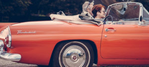 Couple in a red Thunderbird car