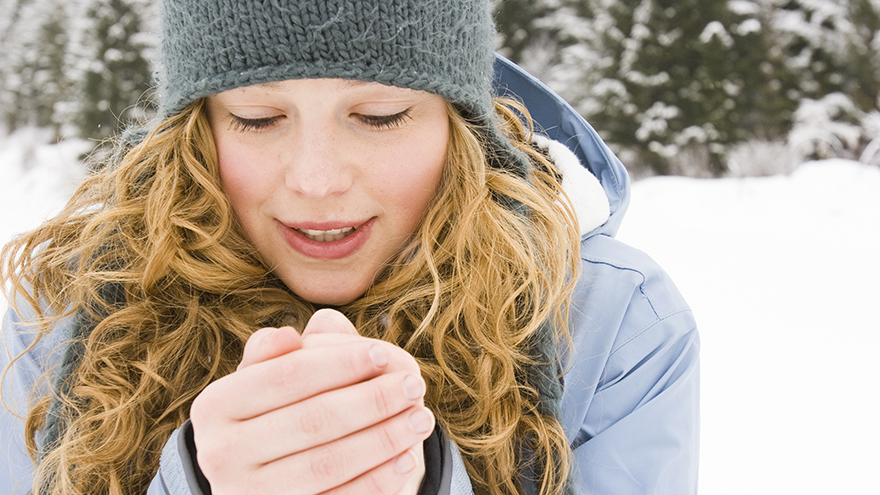 Young woman in woollen hat blowing on her hands in the cold