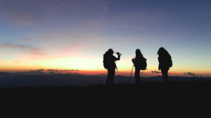 Silhouettes of group hikers people with backpacks enjoying sunset view from top of a mountain.