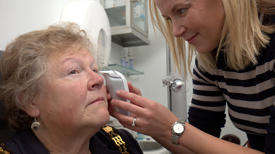 Optometrist Sarah Farrant takes a tear sample from a mature woman