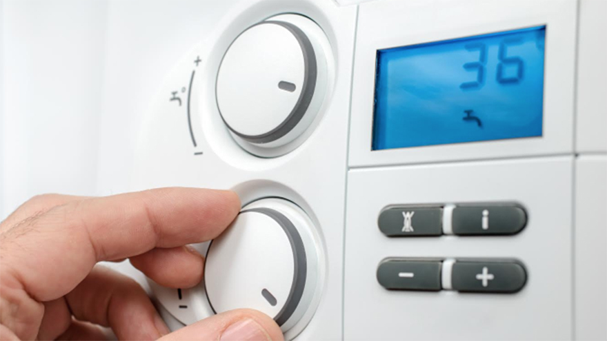 Close up of hand adjusting temperature on heat controls