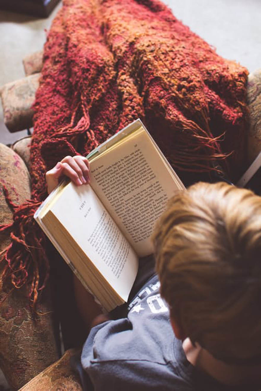 Looking down on someone reading book wrapped in a blanket