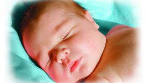 sleeping baby on blue cushion
