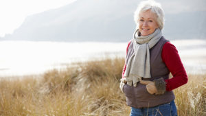 Senior Woman Walking Through Sand Dunes On Winter Beach Smiling