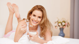 Beautiful woman eating breakfast in bed, looking at camera with a smile.