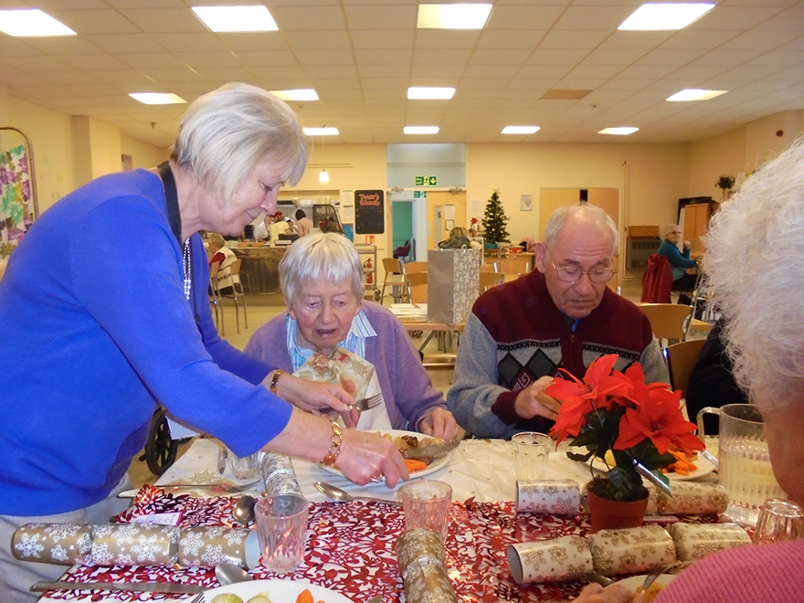 Woman serving Christmas lunch to pensioners