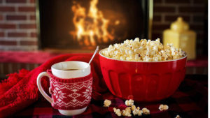 Cup of coffee and bowl of popcorn in front of fire
