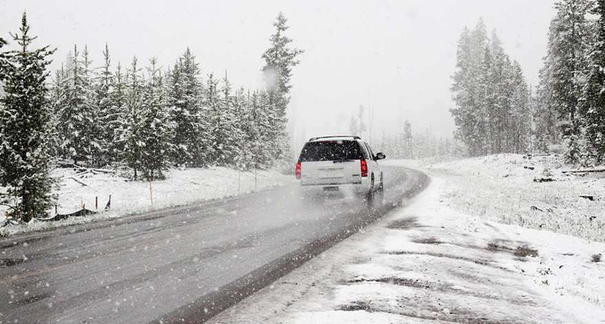 White car driving on snowy road