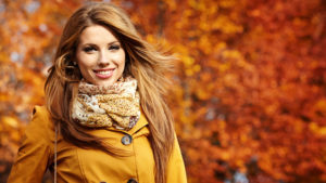 Woman dressed in mustard in park with autumn leaves on tree