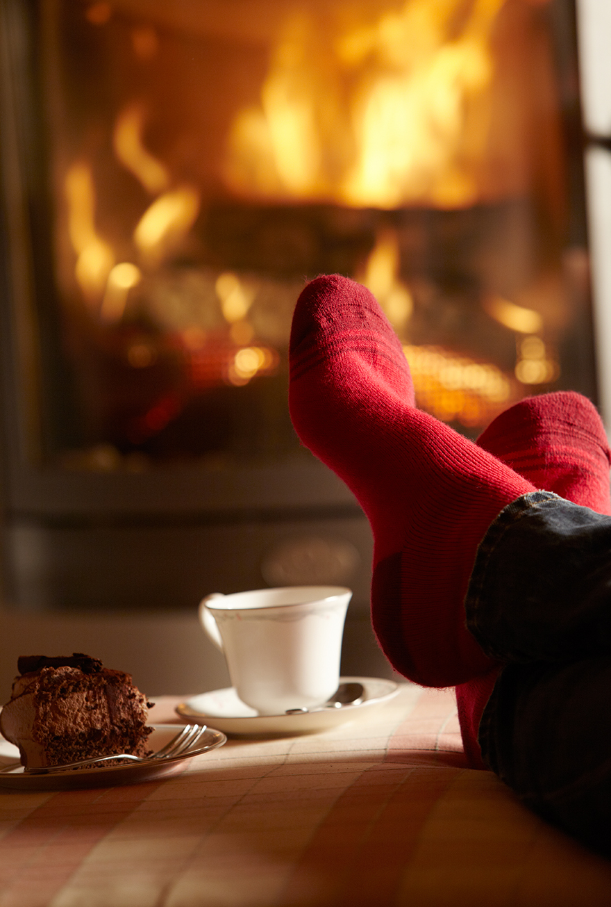 Pair of feet in red socks in front of fire