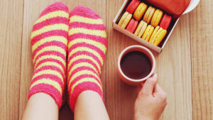 Woman's feet in stripey socks with cup of coffee and macroons