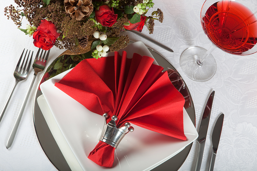 Festive Christmas table with red napkins on a white tablecloth