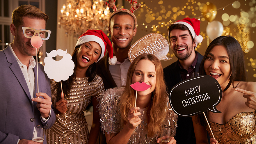 Group Of Friends Dressing Up For Christmas Party Together