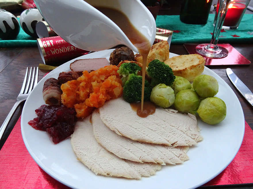 Photo showing some thick homemade gravy being poured over the roast turkey and vegetables of a Christmas dinner, from a white china gravy jug.  The vegetables include Brussels sprouts and a mashed mixture of boiled carrots and swede.