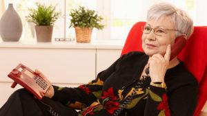 Woman using landline phone sitting in armchair in living room Pic: Istockphoto