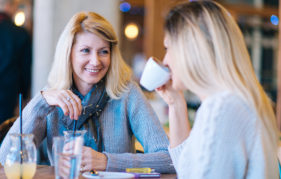 Two women, mature woman about 50 yrs old and young woman 25-30 yrs old, sitting in modern cafe and drinking lemonade and coffee, and chatting in relaxed atmosphere,