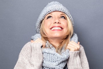dreaming young blond woman with winter hat and imagination feeling cozy, enjoying a happy season holidays, grey background