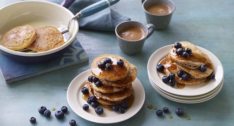 A pancake dripping with syrup and covered in blueberries