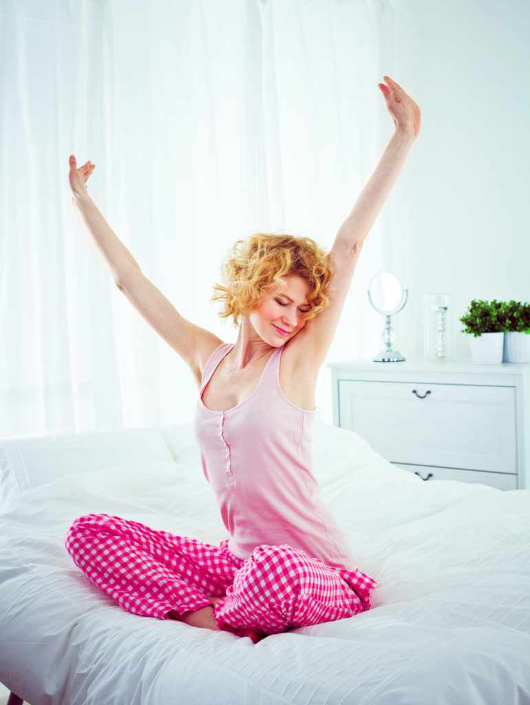 Happy young adult woman sitting cross-legged on a bed in the morning and stretching her arms.