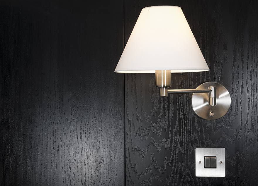 A simple modern lamp and switch on a background of black wood Pic: Istockphoto
