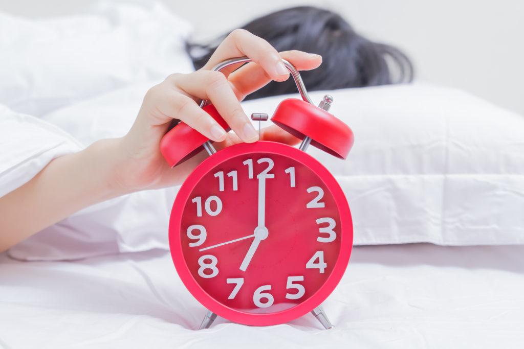 Hand hitting red alarm clock