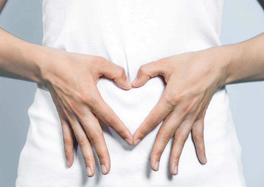 Hands in shape of heart over woman's tummy