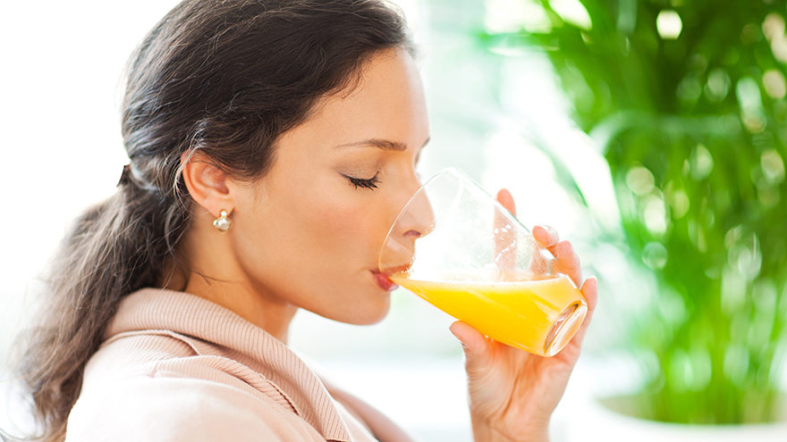 Beautiful woman drinking freshly squeezed orange juice.