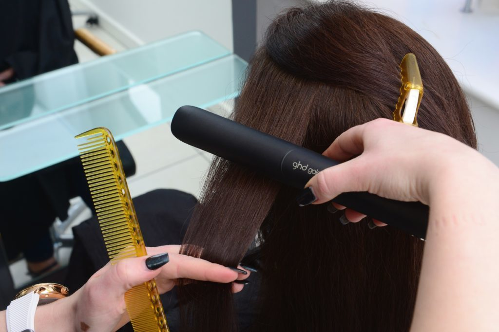 Woman having dark hair straightened