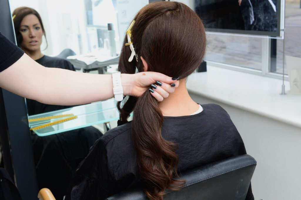 Woman having dark hair drawn to side in ponytail