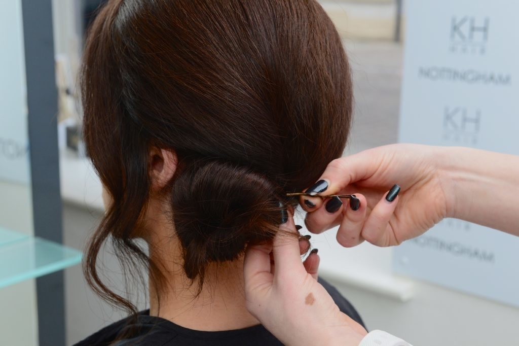 Hair grips being put in dark hair