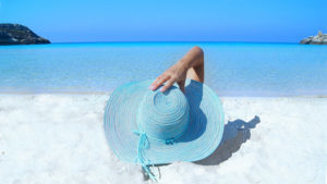 Woman on beach in blue hat