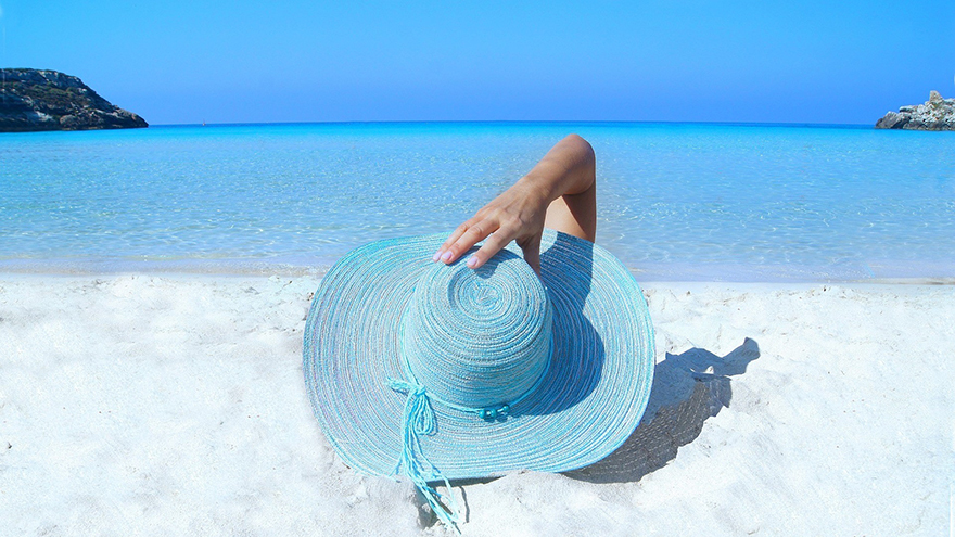 Woman on beach in blue hat